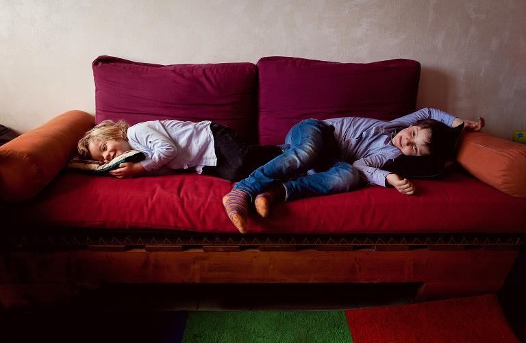 family session, due bambini maschi sdraiati su sofa rosso
