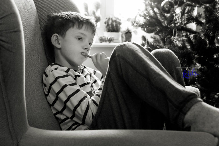 boy is brushing his teeth while sitting in a big armchair