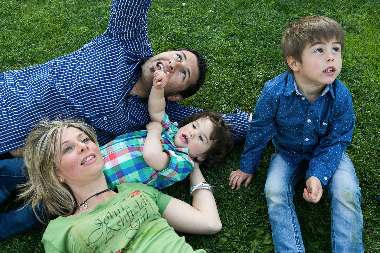 family with two boys playing on grass