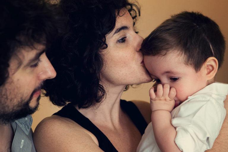 bimbo in braccio alla mamma che li da bacio sulla fronte con il papa che guarda