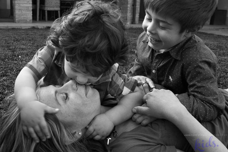 boys are playing with mom on the ground