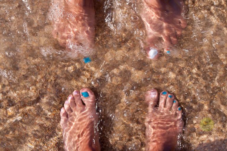 piedi feminili con ughie colorate sul riva di mare, tizzano corsica