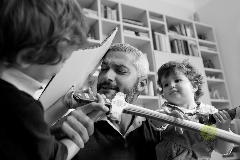 family session, papa gioca a lotta con spada e scudo con due bimbi