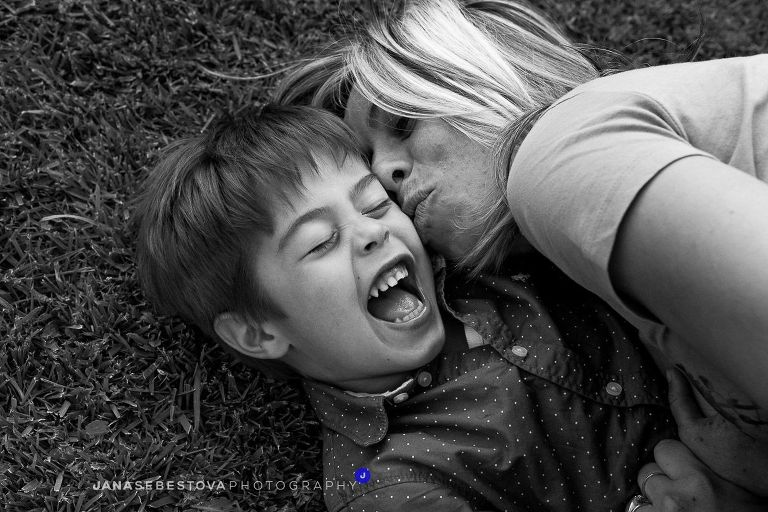 Boy laughing with closed eyes laying on the grass with the mom kissing him