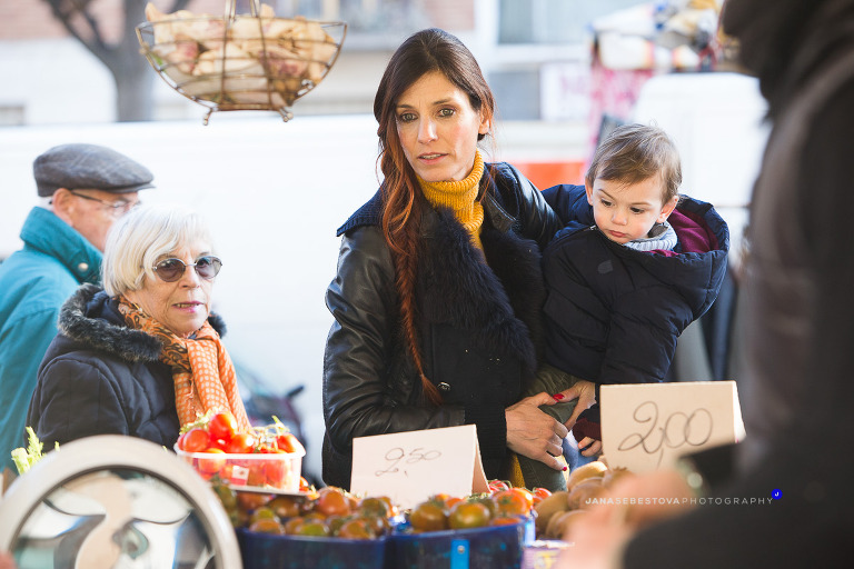 woman with long hair keeps in shoulder the little kid while shopping on outside market