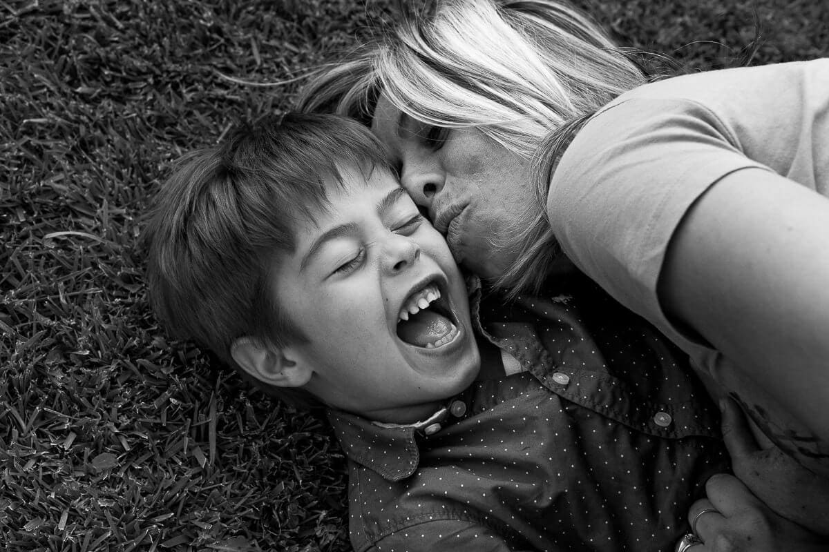 boy kid laying on the grass laughing with mother
