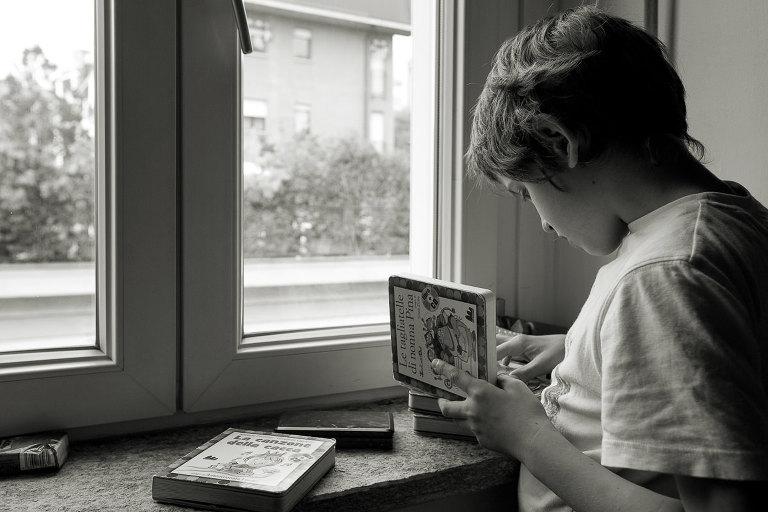 ragazzo legge libro per bambini sulla finestra