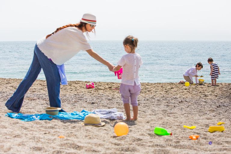 mom with three kids playing on the sea beach