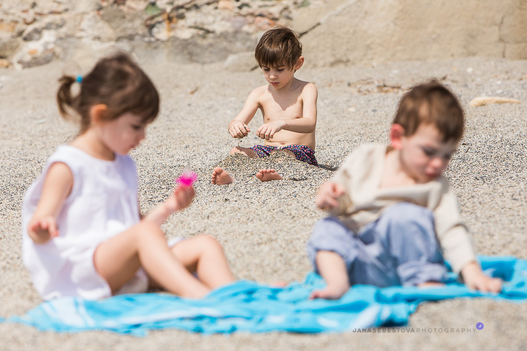 three kids playing on the beach with sand