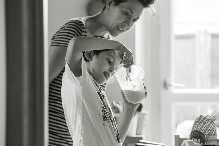 little boy is preparing shaking a milk while mother is watching