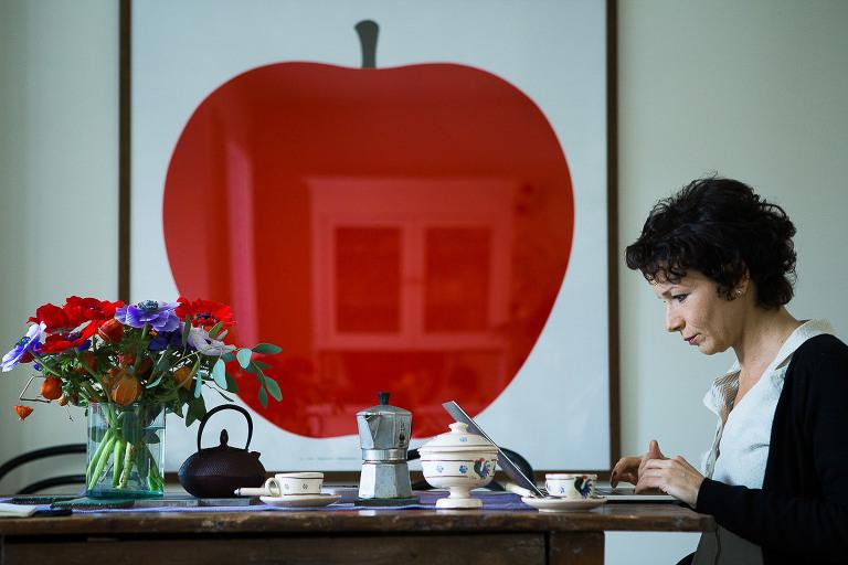 donna seduta al tavolo di fronte a quadro con grande mela