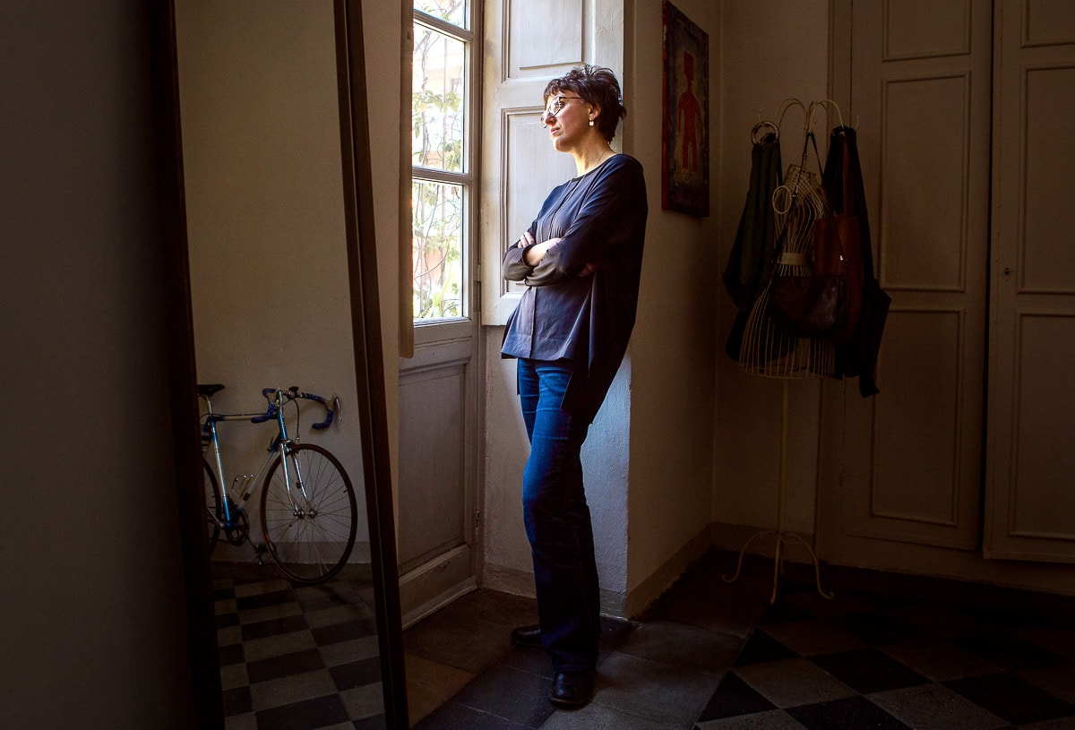 donna in piedi vicino alla finestra guarda fuori