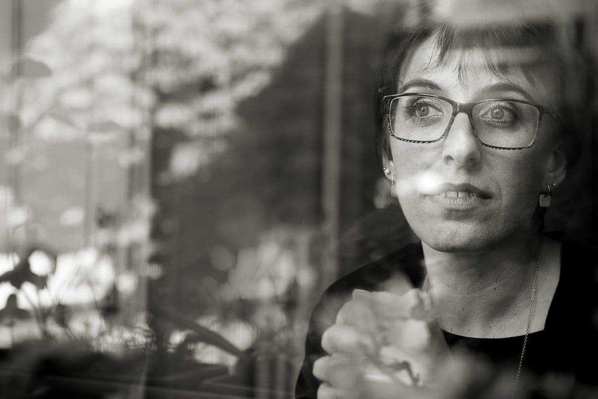 primo piano bianco nero donna attraverso la finestra con i riflessi delle piante