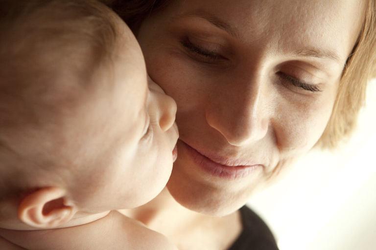viso di mamma che sorride al piccolo bebe che le da bacio