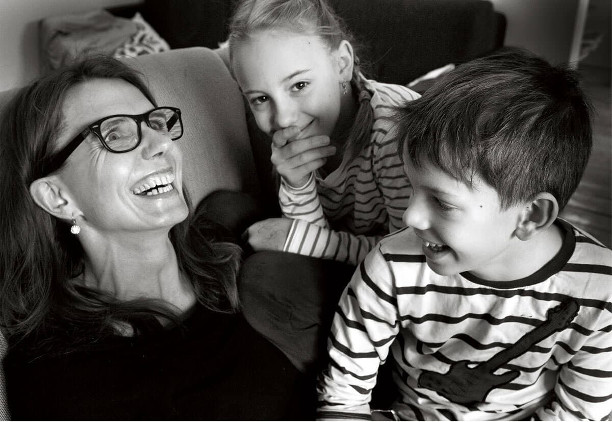 mother laughing together with two kids in armchair