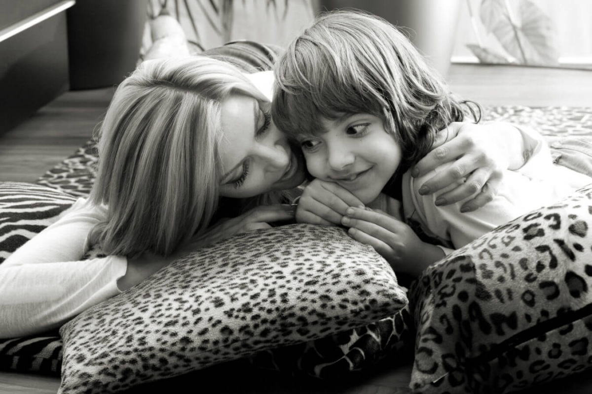 blond mother keeps in arms teen son laying on animalier pillows