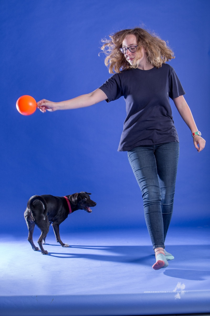 teenage girl is playing with a dog with orange ball