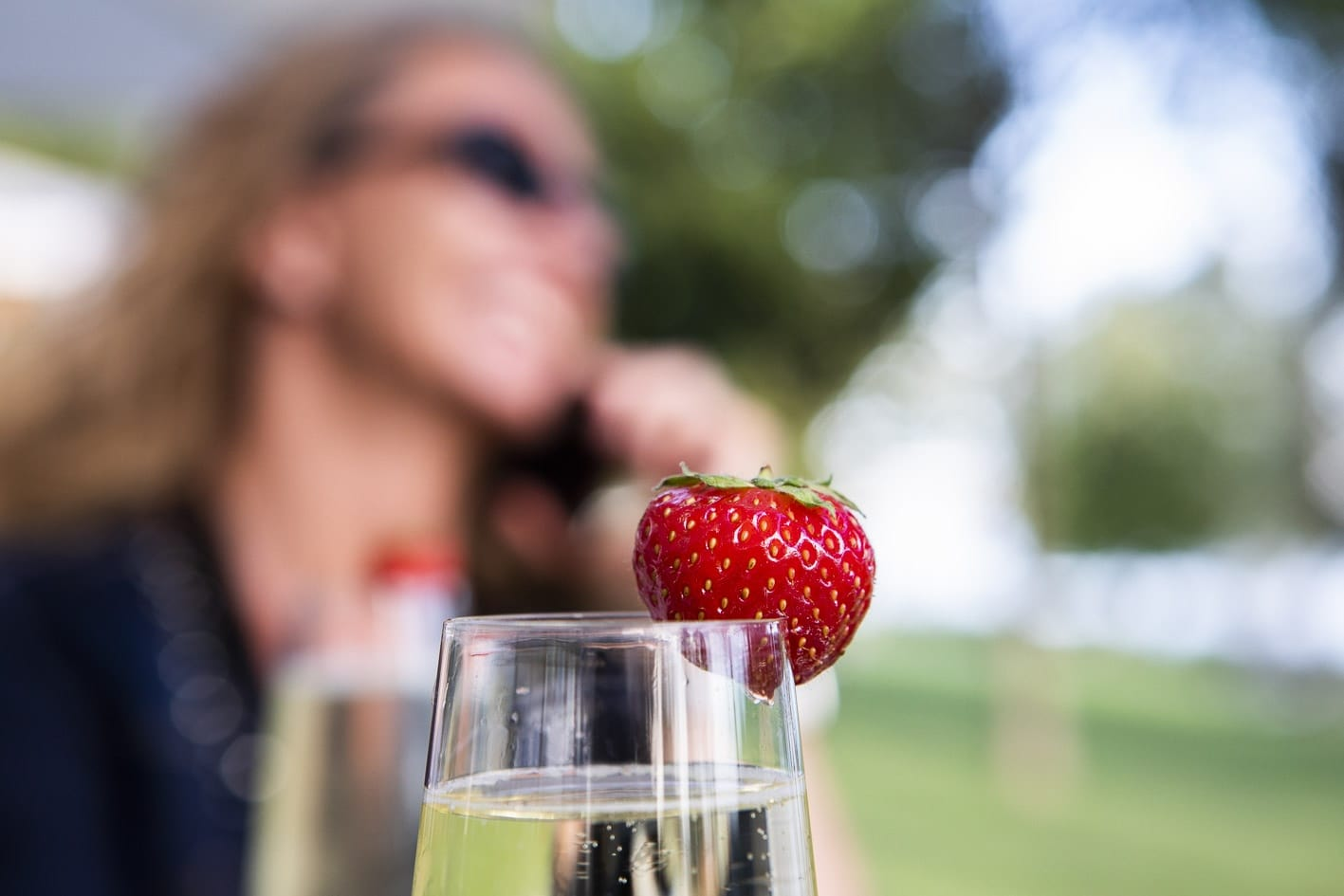 smiling woman on telephone out of focus in background, in front glass of wine with strawberry
