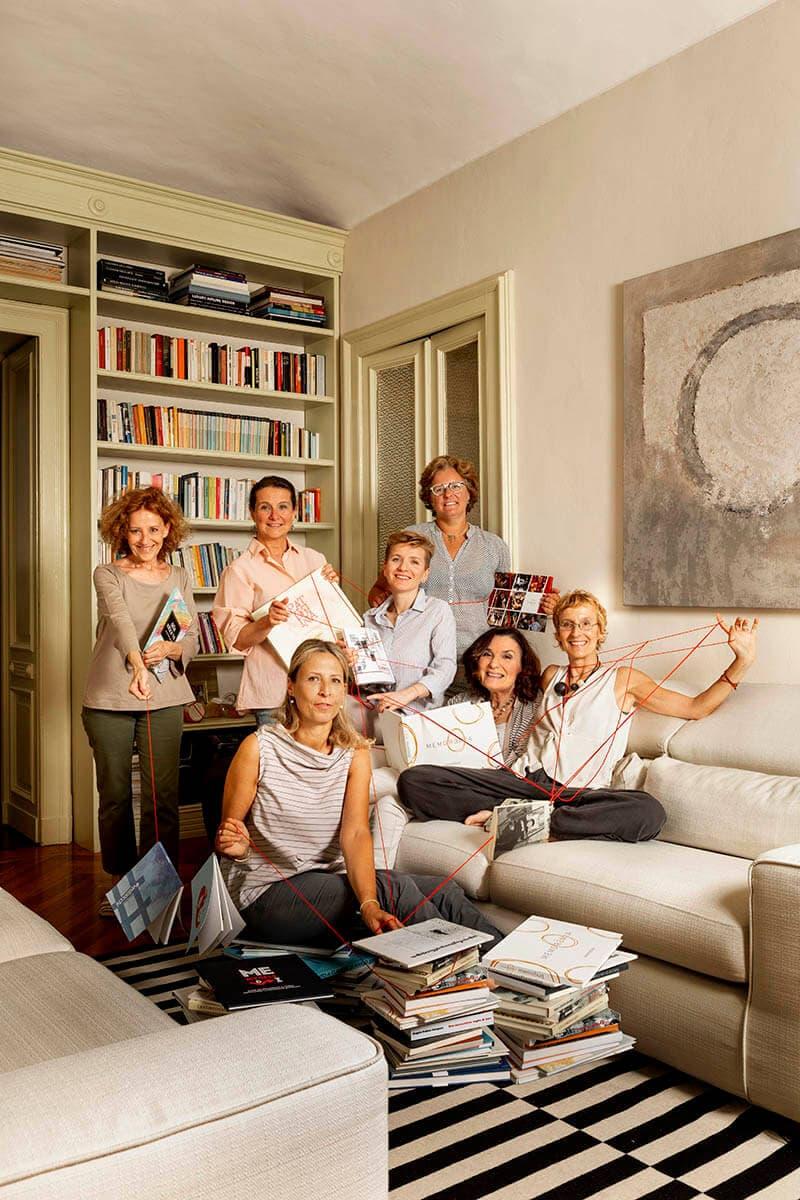 gruppo di donne che ridono in salotto con filo rosso che le unisce