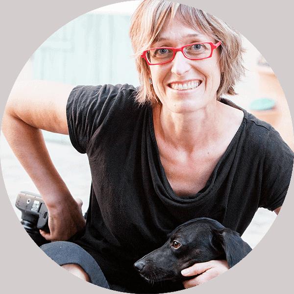donna bionda con occhiali rossi con la macchina foto in mano accarezza cane nero