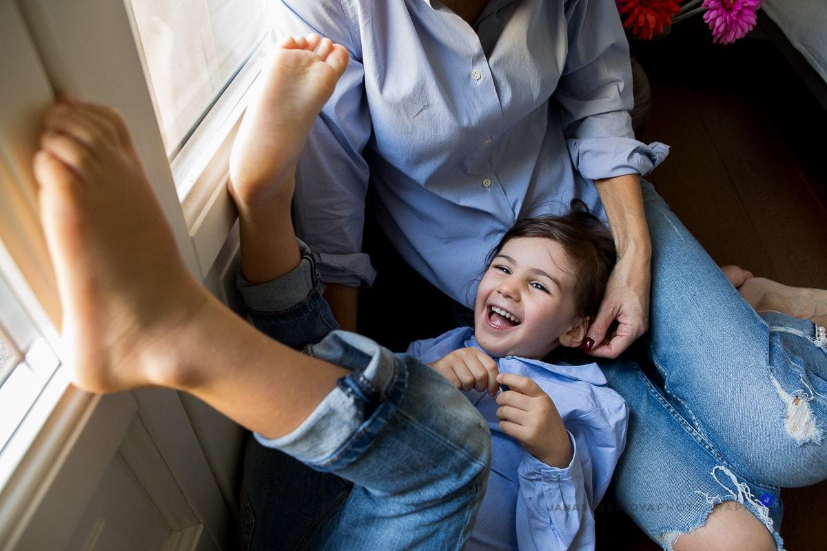 bambina che ride sulle gambe della mamma con piedi per aria